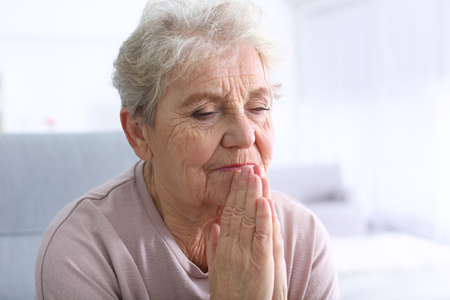 Praying elderly woman at home