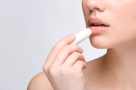 Mujer aplicando bálsamo labial higiénico sobre fondo claro Foto de archivo