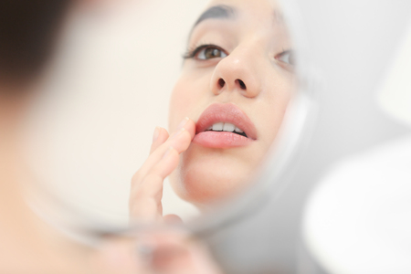 Young woman with cold sore looking in mirror at home Stockfoto