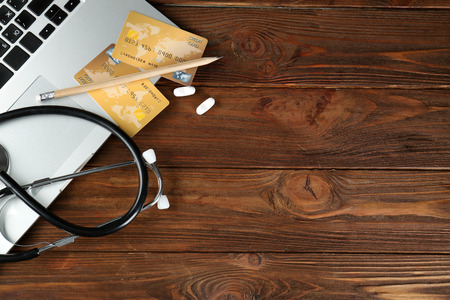 Laptop, stethoscope, pills and credit cards on wooden background