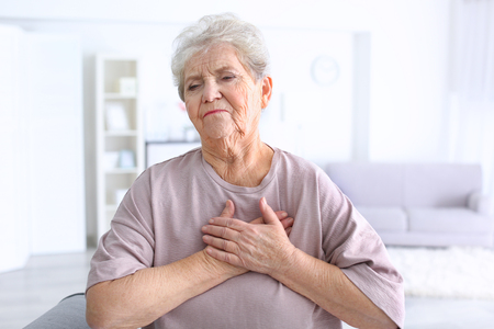 Elderly woman having heart attack at home 스톡 콘텐츠
