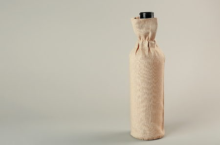 St. Valentine's Day concept. Wine bottle in gift linen pouch on light background