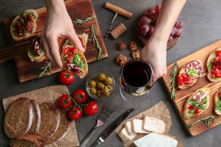 Woman holding glass of wine and tasty snack over table Фото со стока