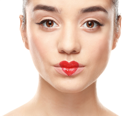 Portrait of beautiful young woman with heart painted on lips, against white background Stock Photo