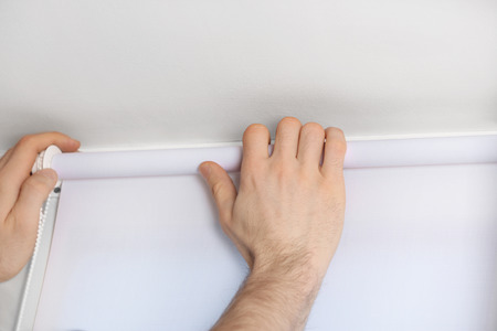 Male hands installing roller blinds on window