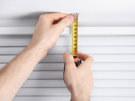 Male hands making window measurements