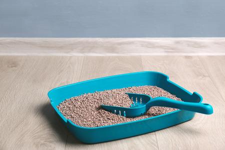 Katzentoilette mit Füllstoff und Schaufel auf dem Boden