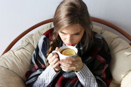 Young ill woman drinking hot tea with lemon while sitting on lounge at home Stock fotó