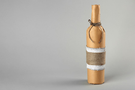 St. Valentines Day concept. Wine bottle in gift wrap on light background