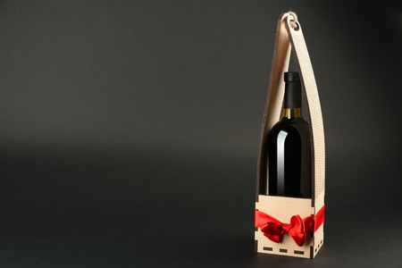 St. Valentines Day concept. Wine bottle in gift box with satin ribbon on dark background