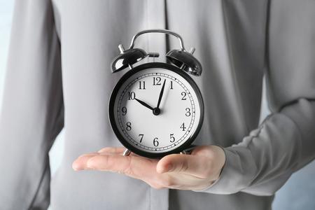 Woman holding vintage alarm clock Banco de Imagens