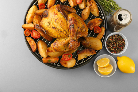Grilled beer can chicken with vegetables on table Stock Photo