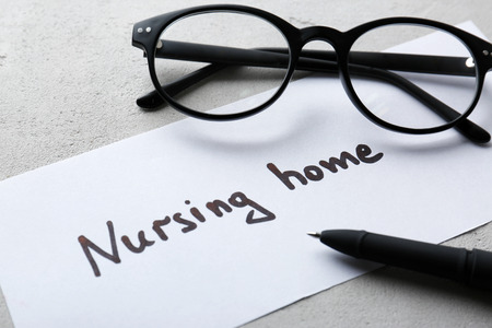 Eyeglasses and paper sheet with text NURSING HOME on light background