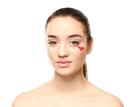 Beautiful young woman with heart painted on face, against white background