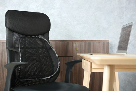 Office chair with mesh for back support and laptop on table, indoors Stock Photo