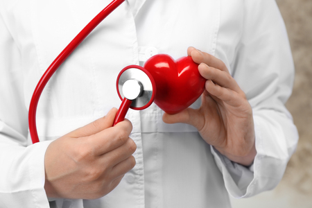 Doctor holding stethoscope and plastic heart, closeup Stok Fotoğraf