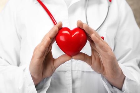 Doctor holding plastic heart in hands, closeup Stok Fotoğraf