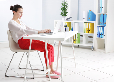 Incorrect posture concept. Young woman sitting at table in modern room
