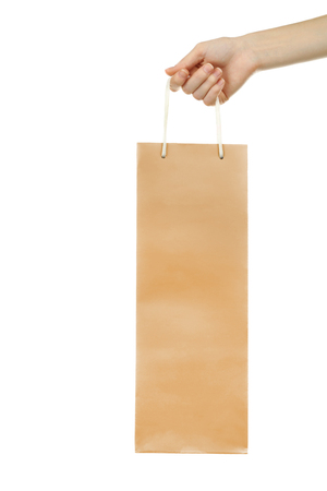 Female hand holding gift paper bag on white background