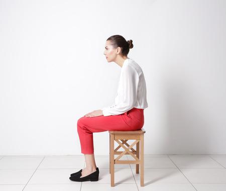 Concepto de postura incorrecta. Mujer joven sentada en un taburete contra el fondo de la pared blanca Foto de archivo