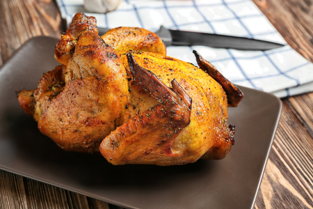 Plate with roasted beer can chicken on wooden background