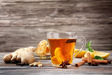 Hot drink with honey and lemon for cough remedy on wooden table