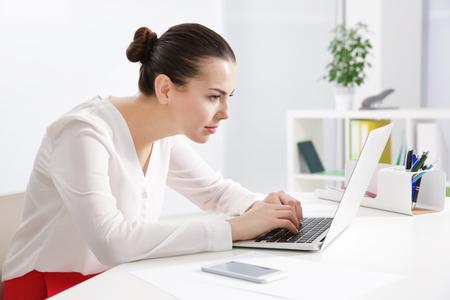 Concetto di postura scorretta. Giovane donna seduta a tavola in una stanza moderna