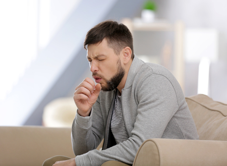 Young ill man sitting on sofa at home