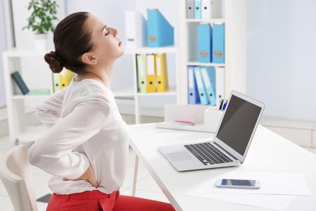 Concetto di postura scorretta. Giovane donna con mal di schiena seduta a tavola in una stanza moderna