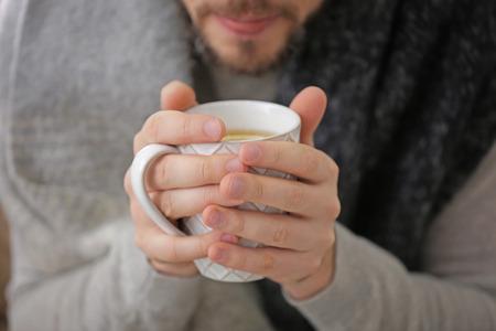 Young ill man drinking hot tea, closeup