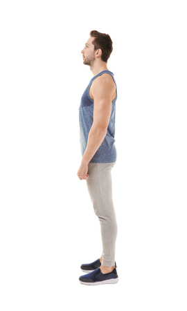 Incorrect posture concept. Man in sport wear isolated on white background. 版權商用圖片