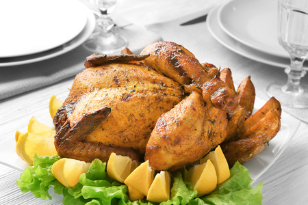 Plate with roasted beer can chicken on table Stock Photo
