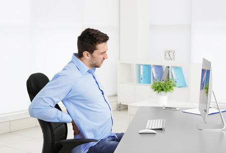 Incorrect posture concept. Man sitting at office table Banco de Imagens
