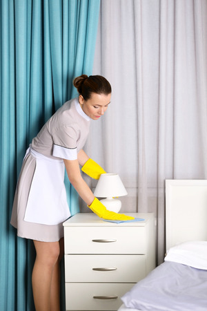 Hotel service concept. Chambermaid cleaning bedside table from dust