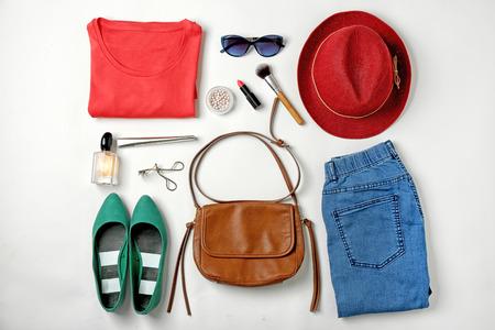 Zestaw stylowych ubrań i kosmetyków dla kobiety na białym tle