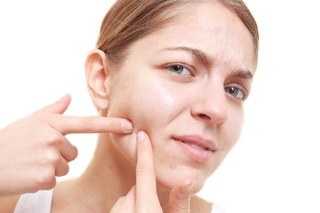 Beautiful young woman popping pimples, on white background