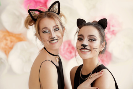 Beautiful young women with cat makeup and ears at party Stock Photo