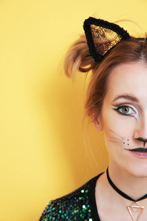 Beautiful young woman with cat makeup and ears on color background, closeup