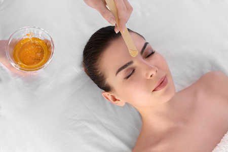 Beautician depilating young woman's face with wax in spa center Foto de archivo