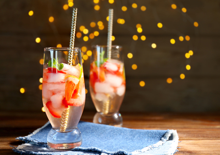 Glass of delicious wine spritzer on blurred lights background