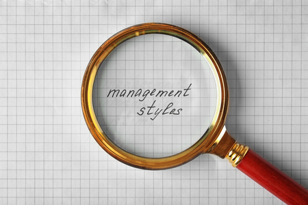 Text MANAGEMENT STYLES under magnifier on paper sheet background