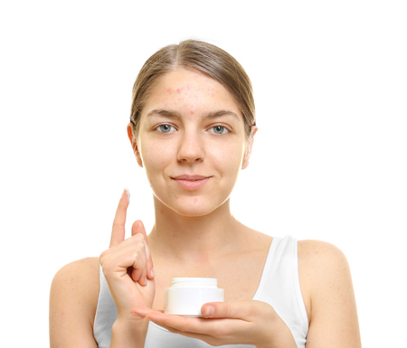 Beautiful young woman with cream for problem skin on white background