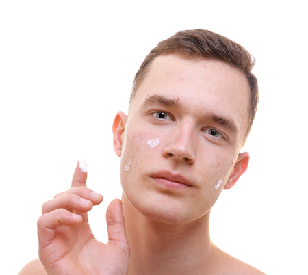Handsome young man applying cream for problem skin onto face, on white background Stock Photo
