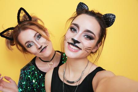 Hermosas mujeres jóvenes con maquillaje de gato y orejas sobre fondo de color