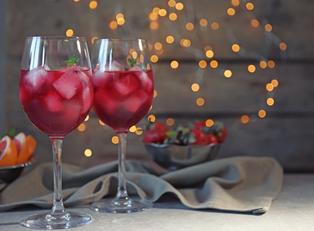Glasses of delicious wine spritzer on blurred lights background