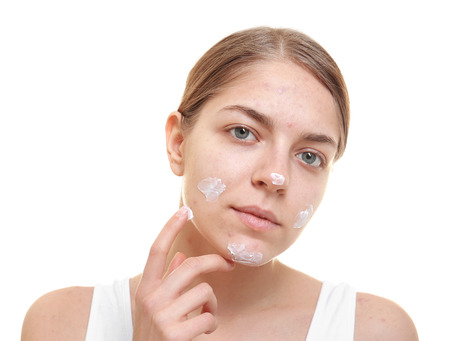Beautiful young woman applying cream for problem skin onto face, on white background Stock Photo