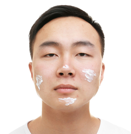 Young Asian man with cream for problem skin applied onto face, on white background