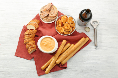 Bowl with beer cheese dip and snacks on wooden table Stock fotó