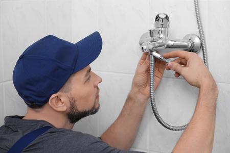 Plumber repairing faucet in shower, closeup