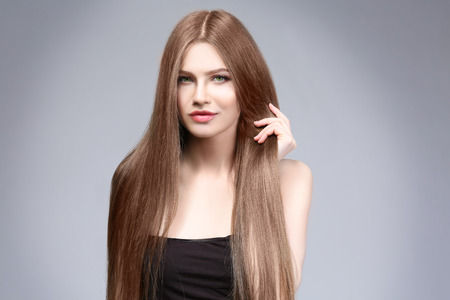 Attractive young woman with beautiful long hair on light background
